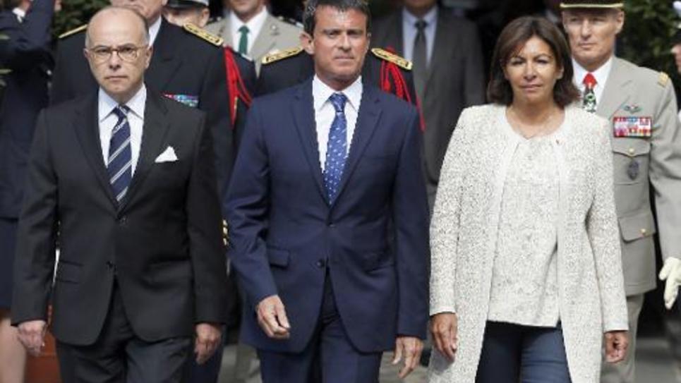 Le ministre de l'Intérieur Bernard Cazeneuve, le Premier ministre Manuel Valls et la maire Anne Hidalgo lors de d'une cérémonie commémorant la libération de la capitale, le 19 août 20104 à la Préfecture de Paris