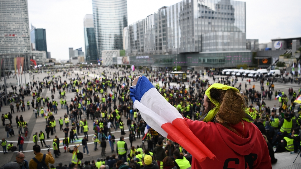 """Un manifestant brandit le drapeau français lors d'une manifestation de """"gilets jaunes"""", le 6 avril 20196 à Paris"""