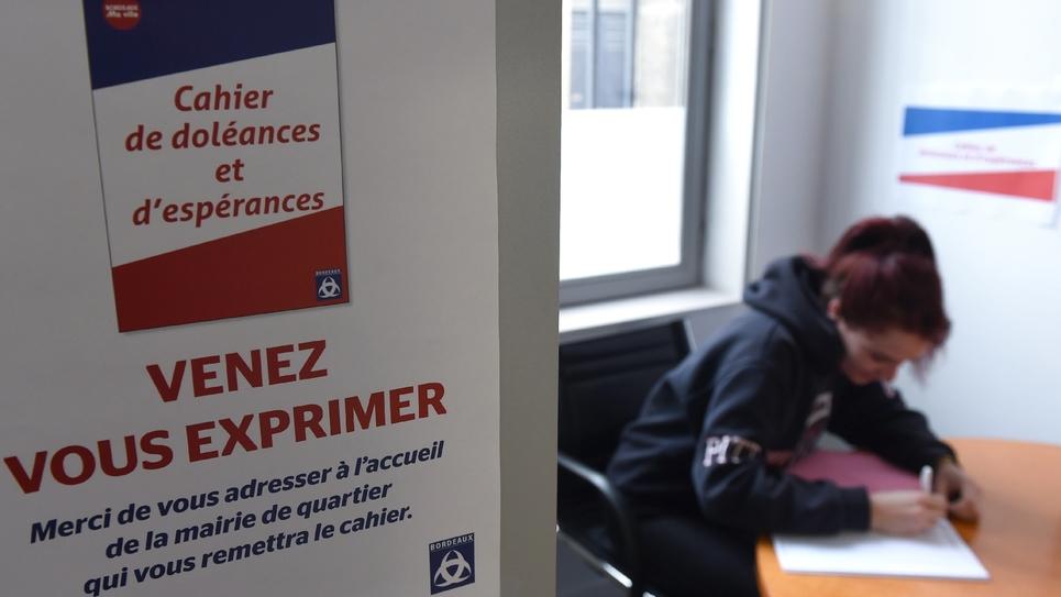 """Une femme inscrit ses doléances sur le """"cahier de doléances et d'espérances"""" mis à disposition dans huit mairies de quartier à Bordeaux, le 18 janvier 2019"""