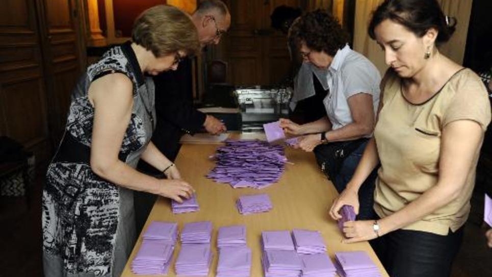 Des bénévoles comptent des bulletins de vote au terme du premier tour des municipales partielles à Clichy, dans les Hauts-de-Seine, le 14 juin 2015