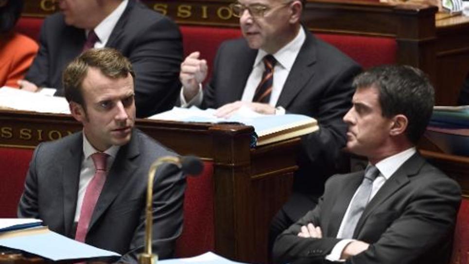 Le Premier ministre Manuel Valls s'entretient avec le ministre de l'Economie Emmanuel Macron, lors d'une session à l'Assemblée le 21 octobre  2014