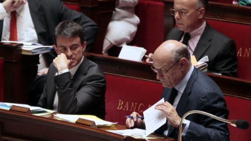 Le Premier ministre Manuel Valls (g) et le ministre des Finances Michel Sapin à l'Assemblée Nationale, le 1er juillet 2014