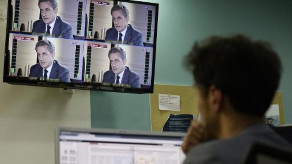 Un journaliste regarde l'interview de Nicolas Sarkozy sur TF1 à 20h le 2 juillet 2014 à Paris