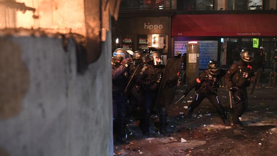 Des policiers se mettent à couvert lors de heurts avec des manifestants, le 28 novembre 2020 à Paris