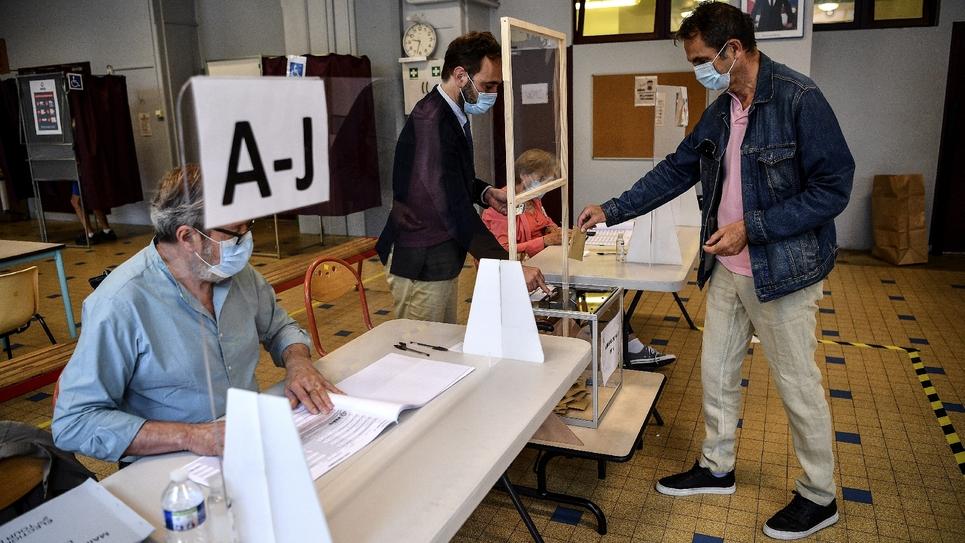 Un homme portant un masque met son bulletin dans l'urne dans un bureau de vote du 5e arrondissement de Paris lors du second tour des élections municipales le 28 juin 2020