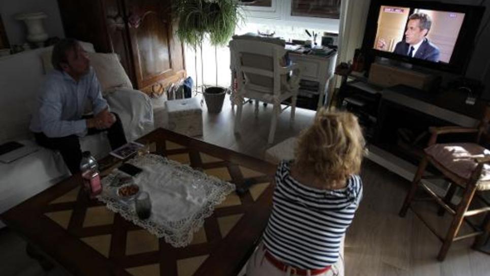 Des téléspectateurs regardent l'ancien président Nicolas Sarkozy à la télévision, le 2 juillet 2014 à Caen