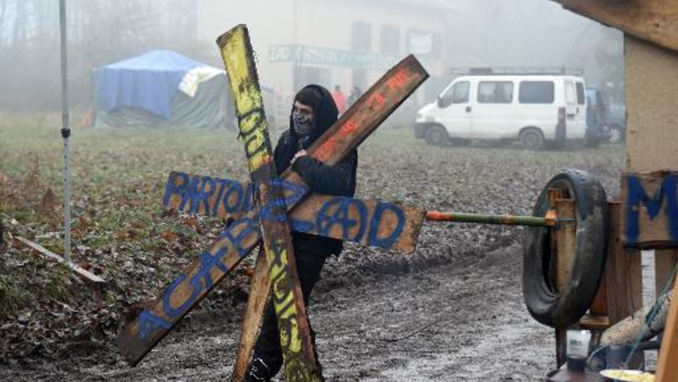 Un activiste met en place une barrière devant une maison occupée pour protester contre un projet de village de vacances Center Parc dans la forêt de Chambaran, le 4 décembre 2014 à Roybon (Isère)