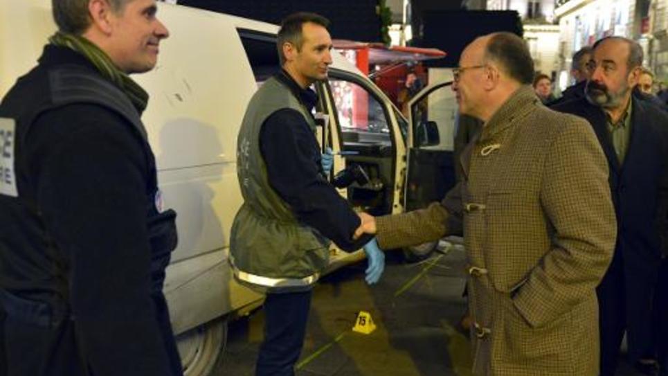Le ministre de l'Intérieur Bernard Cazeneuve avec des officiers de police le 22 décembre 2014 à Nantes où un automoboliste a foncé sur le marché de Noël