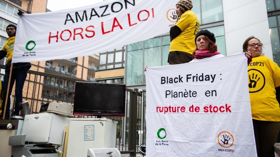 """Des membres de l'ONG """"Les Amis de la Terre"""" dénoncent les méthodes du géant de la vente sur internet Amazon devant son siège social français à Clichy, le 23 novembre 2018"""