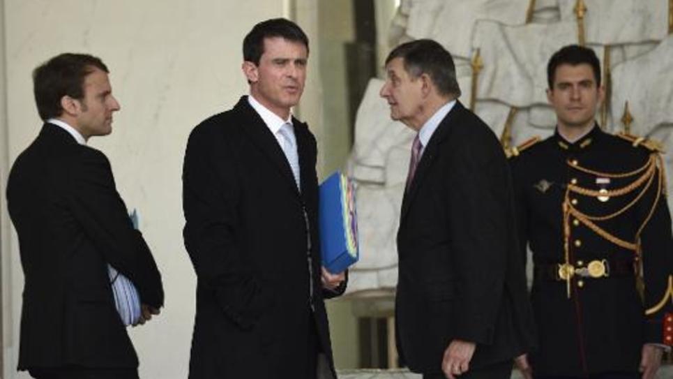 Le Premier ministre Manuel Valls et le ministre de l'Economie Emmanuel Macron (g) quittent l'Elysée après le Conseil des ministres le 4 mars 2015