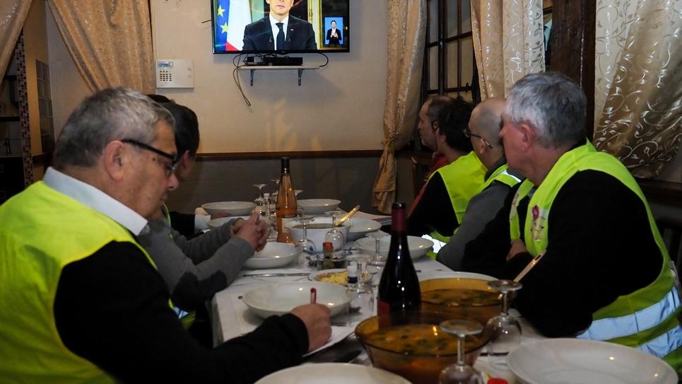 """Des """"gilets jaunes"""" regardent l'intervention d'Emmanuel Macron à la télévision dans un restaurant à Fay-au-Loges, le 10 décembre 2018"""