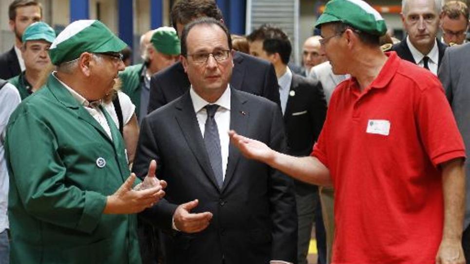 Le chef de l'Etat François hollande (c) écoute le 4 juin 2015 deux employés de la nouvelle société coopérative ouvrière provençale de thés et infusions, la Scop-Ti, ex-Fralib