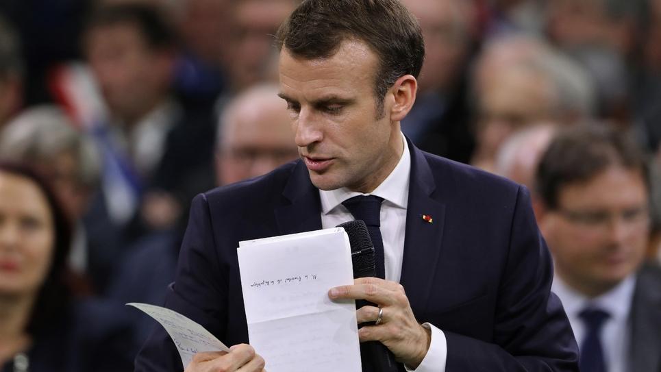 Emmanuel Macron écoute une élue lors du lancement du grand débat national devant les maires normands à Grand Bourgtheroulde, dans l'Eure, le 15 janvier 2019