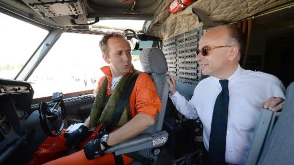 Le ministre de l'Intérieur Bernard Cazeneuve (d) parle avec le pilote d'un Canadair, le 31 juillet 2014 à Marignane