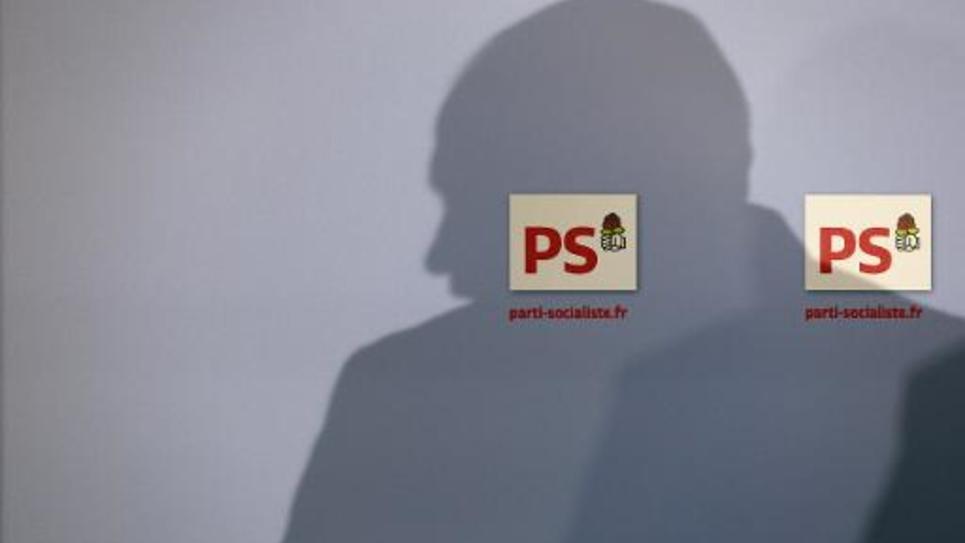 Une ombre sur un mur où figurent deux logos du Parti socialiste, en 2014