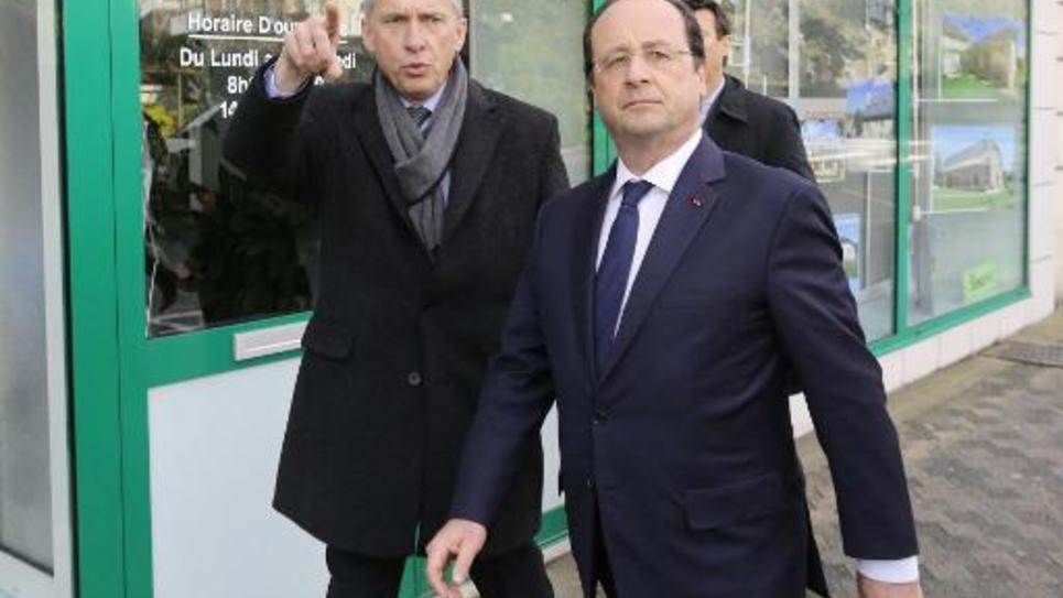 Le président de la République française François Hollande dans les rues de Tulles en compagnie du maire socialiste de la ville, Bernard Combes, le 23 mars 2014