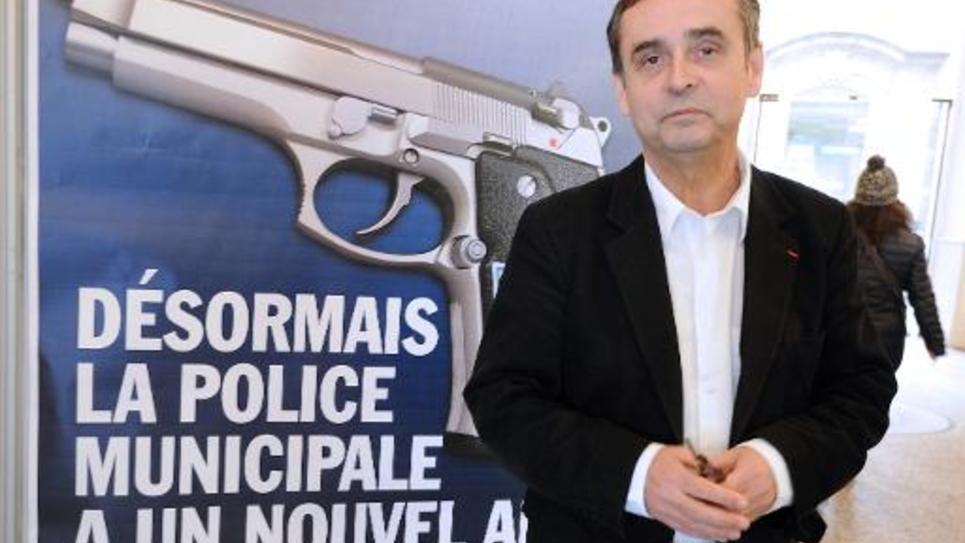 """Le maire de Béziers Robert Ménard pose devant l'affiche présentant un pistolet en gros plan comme le """"nouvel ami"""" de la police municipale à Béziers le 11 février 2015"""