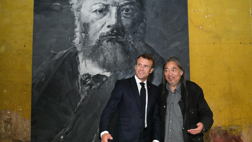 Le président de la République Emmanuel Macron et l'artiste franco-chinois Yan Pei-Ming devant un tableau de Gustave Courbet peint par l'artiste à Ornans le 10 juin 2019