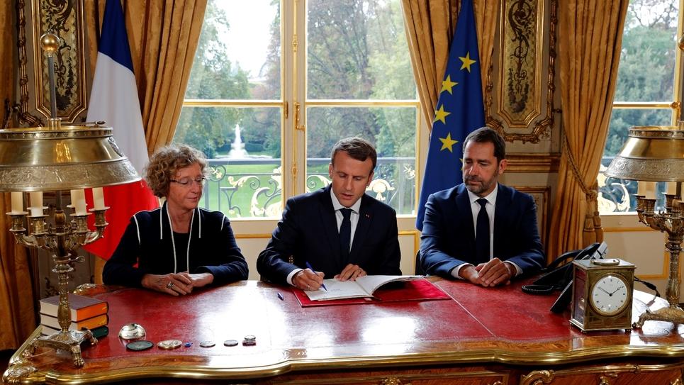 Le président E. Macron (C) signe les ordonnances réformant le code du travail aux côtés de la ministre du Travail, M. Pénicaud (G), et de C. Castaner (D), porte-parole du gouvernement et secrétaire d'État des Relations au Parlement, le 22 septembre 2017 à