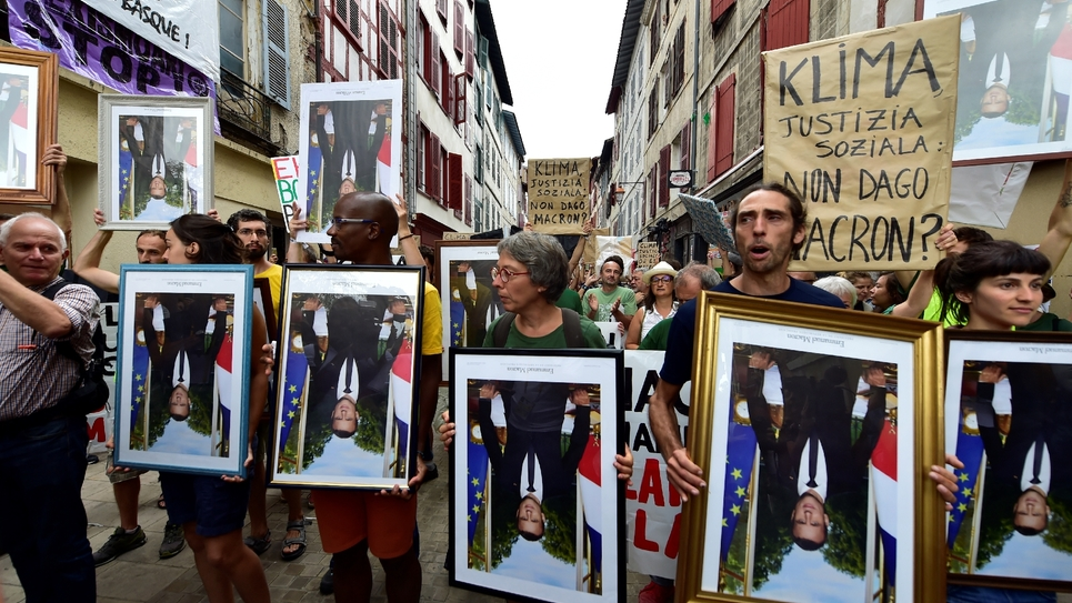 """Des manifestants anti-G7 """"pour le climats et la justice sociale"""" brandissent des portraits du président Macron décrochés depuis des mois dans des mairies, le 25 août 2019 à Bayonne"""