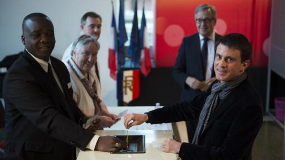 Le Premier ministre Manuel Valls (d) dépose son bulletin dans l'urne lors du 2e tour des élections départementales, le 29 mars 2015  à Evry