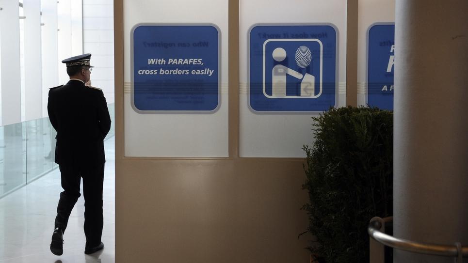 Un officier de police marche, le 19 octobre 2009 à l'aéroport Roissy-Charles de Gaulle, à côté d'un panneau présentant le dispositif Parafes (Passage automatisé rapide aux frontières extérieures Schengen)