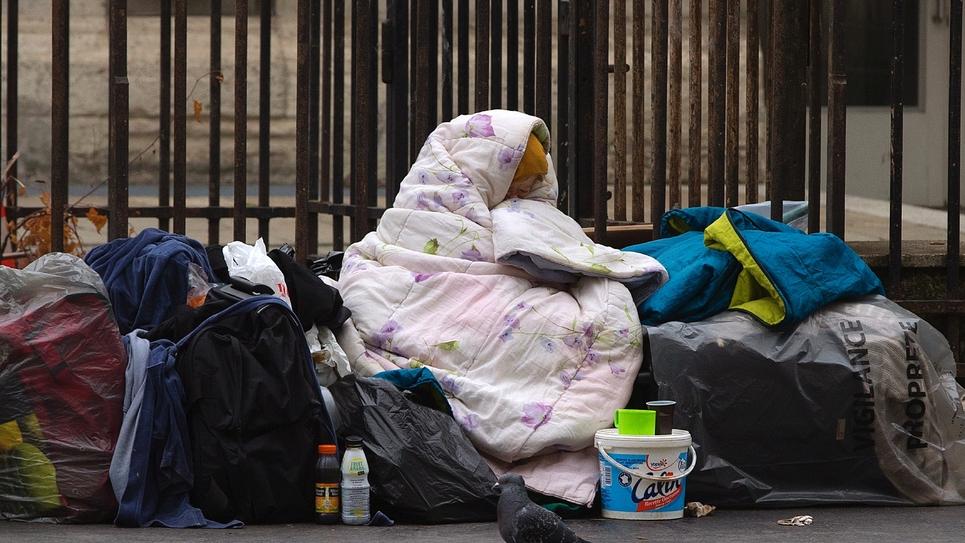 Une femme sans-abris est enveloppée dans une couverture sur le trottoir d'une rue parisienne, le 3 décembre 2014