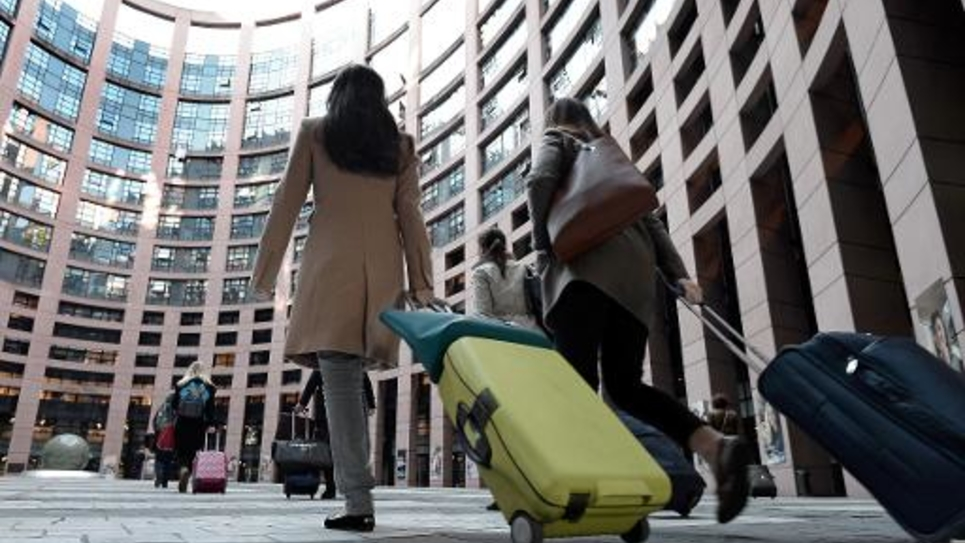 Des députés ou salariés du parlement européen arrivant avec leurs bagages, le 17 avril 2014, dans le bâtiment du parlement européen de Strasbourg où ils se réunissent chaque mois selon un rituel bien rodé