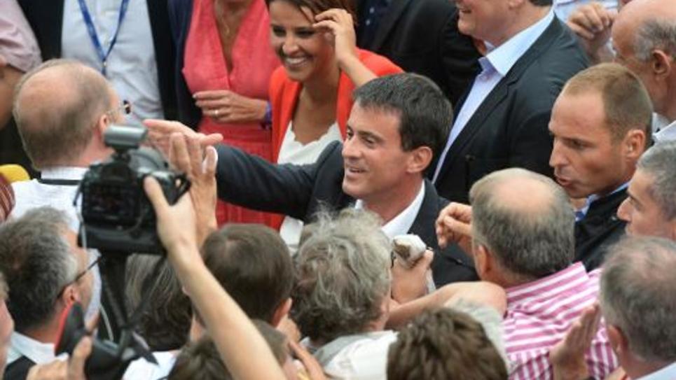 Le Premier ministre Manuel Valls et la ministre de l'Education Najat Vallaud-Belkacem sont accueillis par des militants à l'université d'été à La Rochelle, le 30 août 2014
