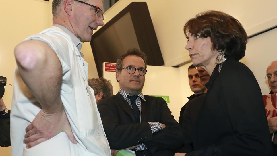 La ministre de la Santé Marisol Touraine (D) et le directeur général de l'Assistance publique-Hôpitaux de Paris (AP-HP) Martin Hirsch (C), s'entretiennent avec Dominique Pateron (G), chef des urgences de l'hôpital St Antoine à Paris le 27 décembre 2016.
