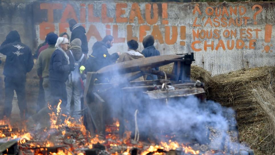Des militants hostiles au projet d'aéroport nantais devant un slogan ciblant Bruno Retailleau, le président de la région Pays de la Loire, sur une barricade dans le territoire qu'ils occupent à Notre-Dame des Landes le 2 décembre 2016