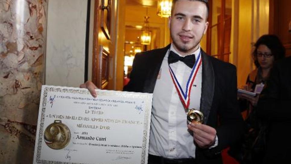 Armando Curri pose après avoir reçu son diplôme de meilleur apprenti menuisier au Sénat, le 4 mars 2015