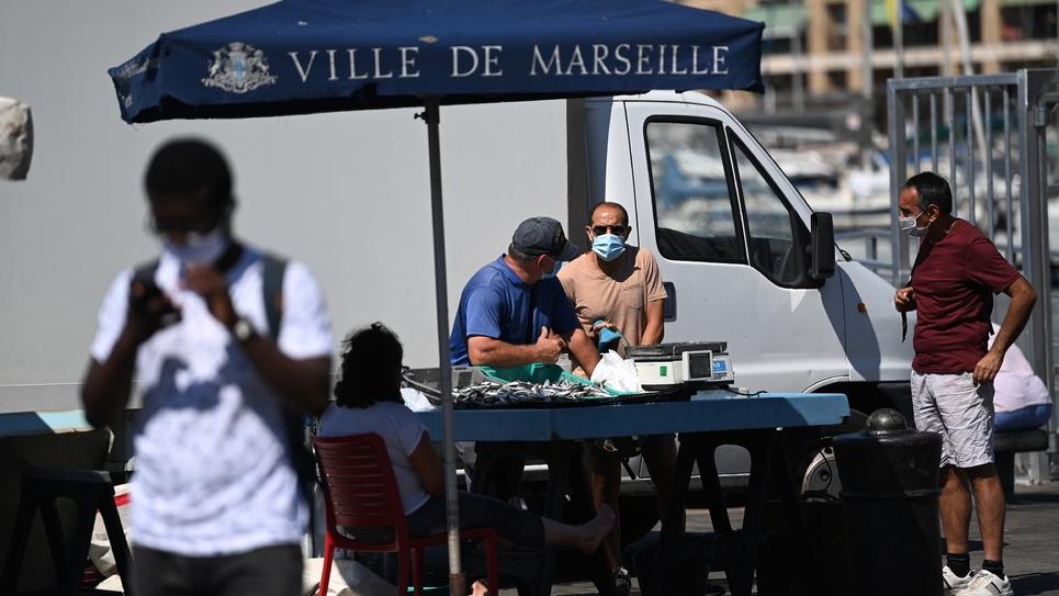 Des vendeurs de rue avec des masques de protection, le 26 août 2020 sur le vieux port à Marseille