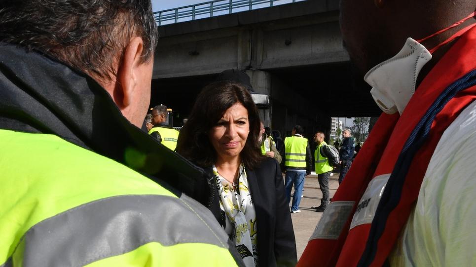 La maire de Paris Anne Hidalgo parle avec des employés municipaux lors de l'évacuation du campement du Millénaire au nord-est de la capitale le 30 mai 2018