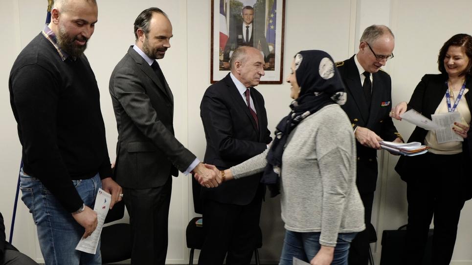 Edouard Philippe et le ministre de l'Intérieur Gérard Collomb (C) serrent la main de réfugiés à Lyon, le 19 février 2018
