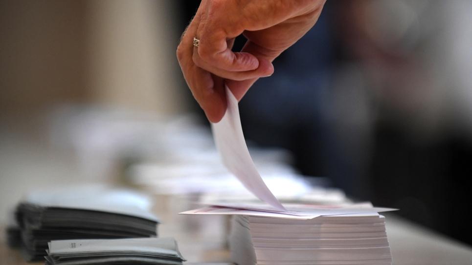 Un électeur prend un bulletin dans un bureau de vote de Carhaix-Plouguer dans le Finistère, en Bretagne, le 11 juin 2017