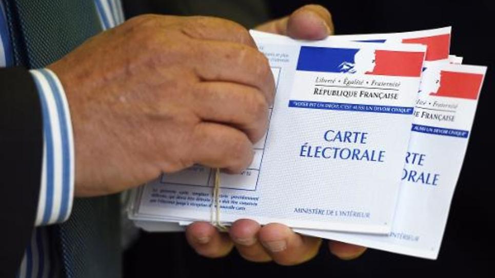 Un volontaire tient un paquet de cartes électorales dans un bureau de vote de Marseille, le 22 mars 2015