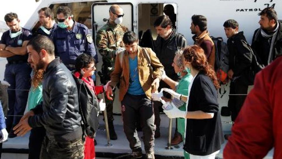 Des demandeurs d'asile syriens, irakiens et afghans débarquent sur le port crétois d'Ierapetra le 27 novembre 2014 après avoir dérivé pendant deux jours en Méditérranée