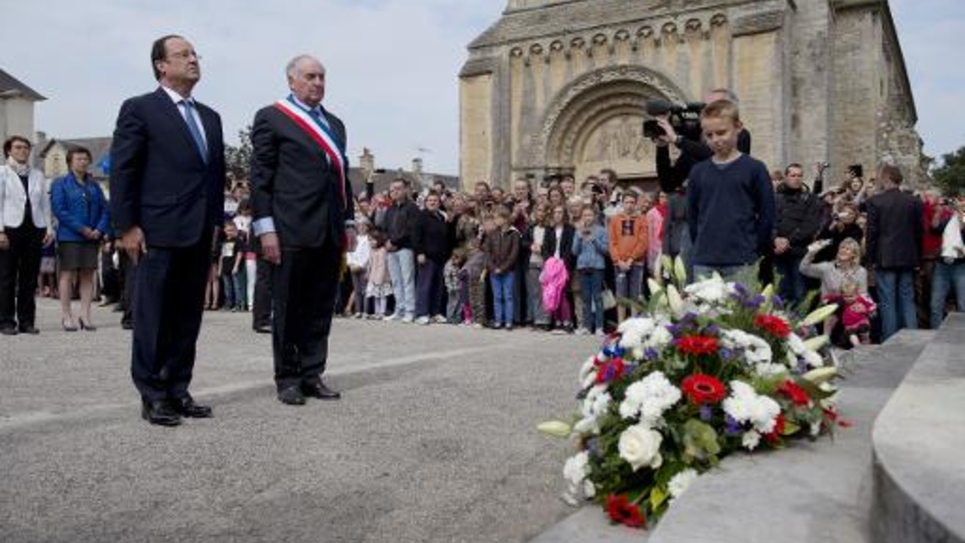 François Hollande (g) et le maire de Trevières (Calvados) lors d'une cérémonie d'hommage aux victimes civiles de la deuxième guerre mondiale en Normandie le 1er juin 2014, en prélude aux commémorations du 70e anniversaire du débarquement allié