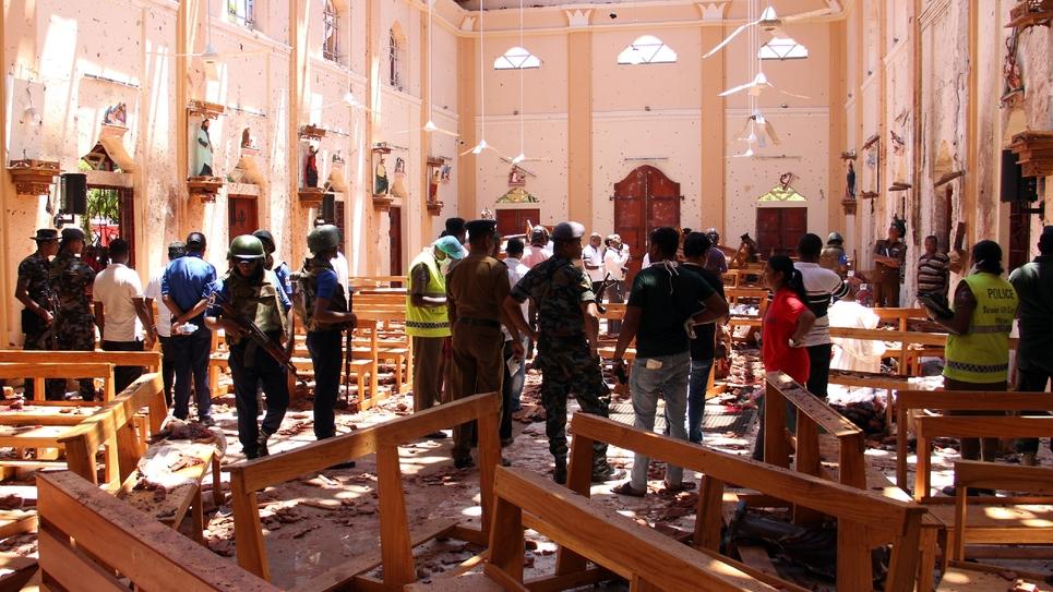 Les forces de sécurité sri-lankaises inspectent les décombres après une explosion à l'intérieur de l'église de Negombo, le 21 avril 2019 à Colombo