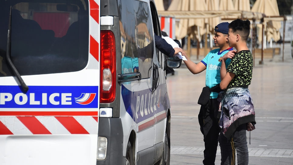 Des policiers contrôlent les attestations de deux adolescents place de la Comédie, le 18 mars 2020 à Montpellier, pendant le confinement instauré en France pour lutter contre le nouveau coronavirus