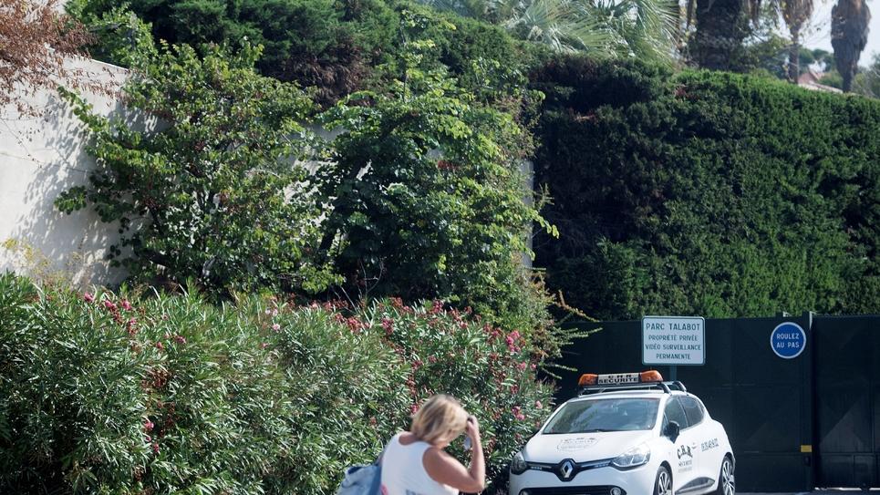 Une femme passe devant l'entrée d'une résidence qui accueillerait pour quelques jours le président Emmanuel Macron et son épouse, le 13 août 2017 à Marseille