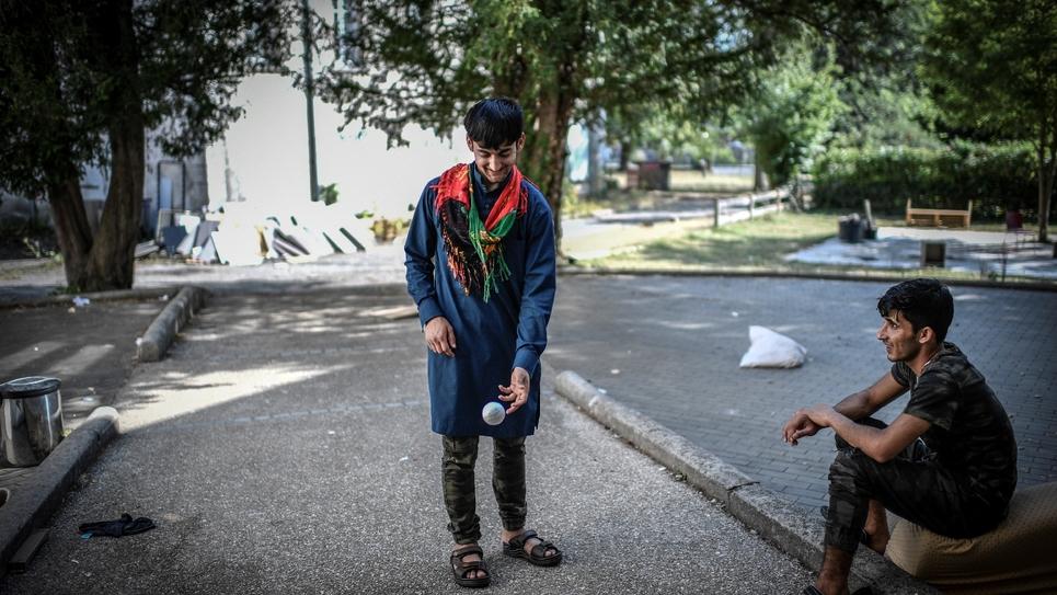 Des migrants afghans échangent dans la cour de leur centre d'hébergement de Forges-les-Bains (région parisienne) le 28 août 2018, peu avant la fermeture du lieu