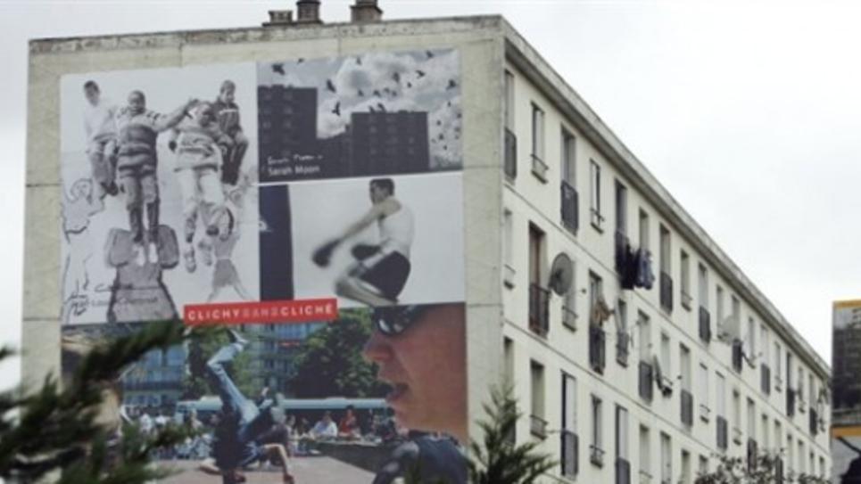 """Clichy-sous-Bois : Vue d'un immeuble drapé de photographies, prise le 12 octobre 2006 à Clichy-sous-Bois. Clichy-sous-Bois accueille ainsi une série d'expositions baptisée """"Clichy sans cliché"""", offrant un autre regard sur cette ville devenue, malgré elle, le symbole des émeutes urbaines il y a un an, après le décès de deux collégiens, morts électrocutés le 27 octobre 2005."""