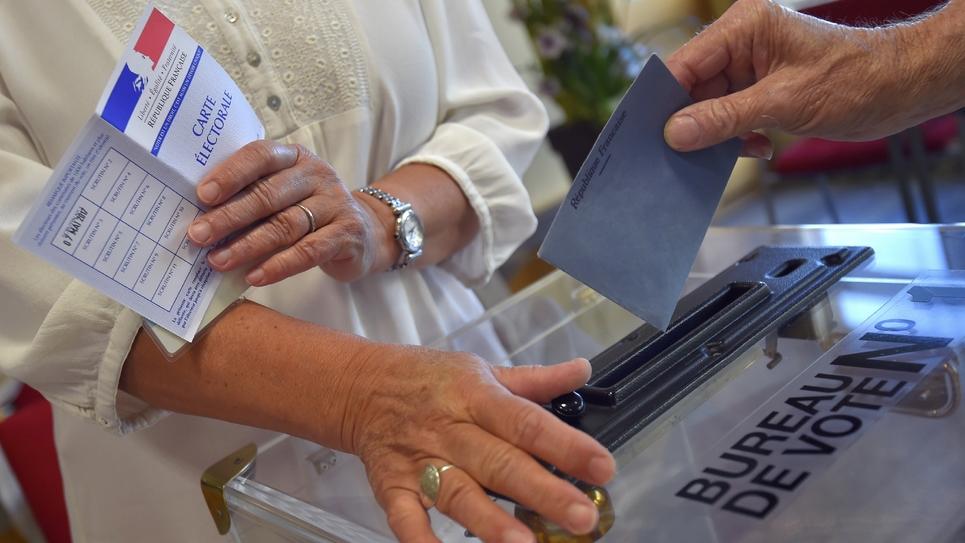 Un homme glisse son bulletin de vote dans l'urne d'un bureau de vote de Vertou (Loire-Atlantique) dans l'Ouest de la France, le 11 juin 2017