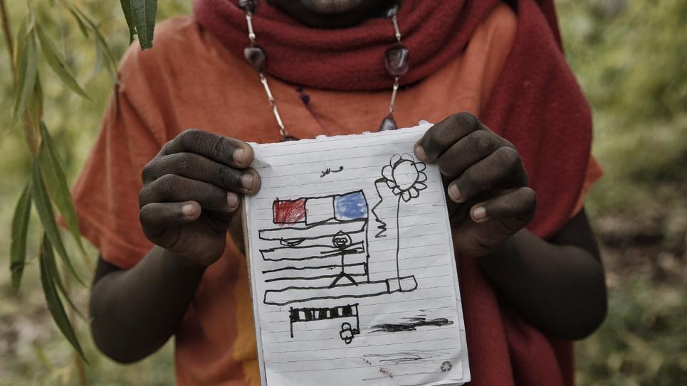 Un enfant montre son dessin dans le jardin de Françoise Cotta, une Française qui accueille des migrants arrivant illégalement en Italie, le 25 octobre 2016 à Breil-sur-Roya, un ancien village franco-italien près de Menton