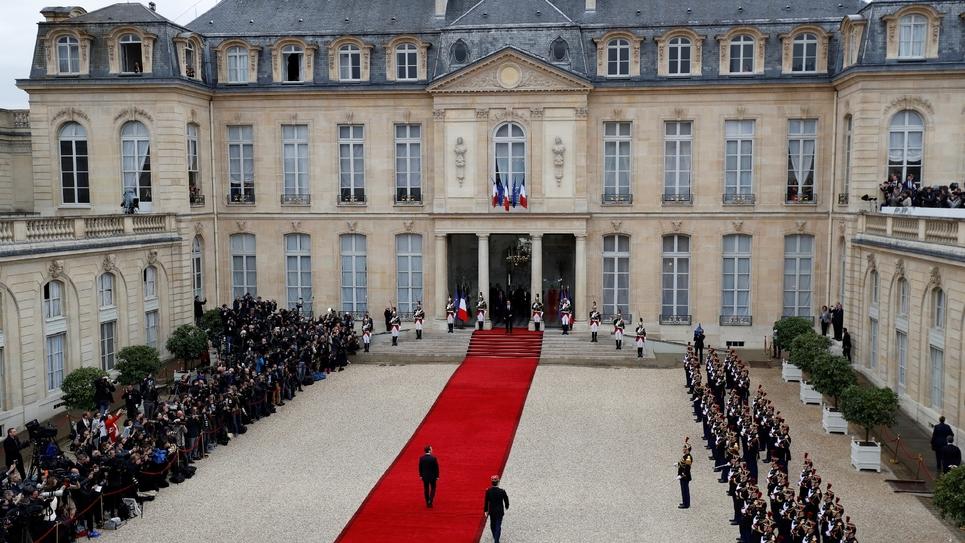 Le président élu Emmanuel Macron sur le tapis rouge menant au perron de l'Elysée où l'attend François Hollande, le 14 mai 2017 à Paris