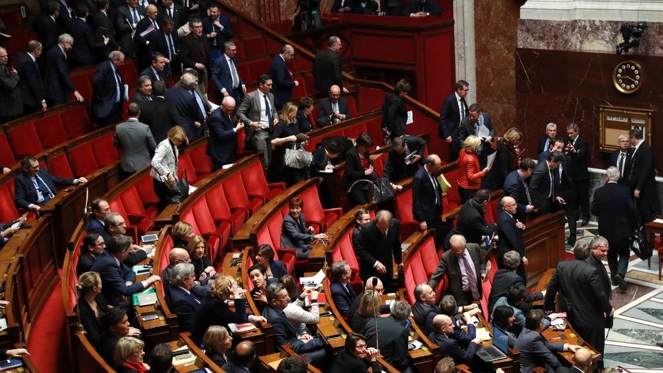 Des députés d'opposition de droite et de gauche quittent l'hémicycle, à Paris le 21 mars 2018