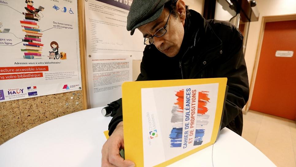 Un homme remplit le cahier de doléances laissé en libre accès dans un centre d'action communal d'action sociale à Charleville-Mézières, le 20 décembre 2018