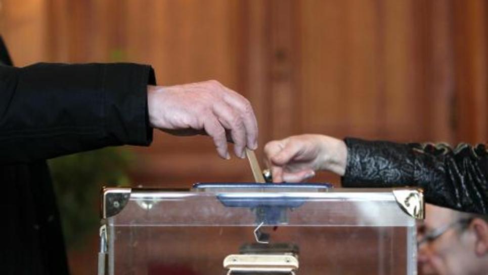 Un homme dépose son bulletin de vote dans l'urne à Rouen le 29 mars 2015 au deuxième tour des élections départementales